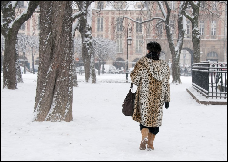 Woman walking through snow in leopard coat, Paris, France, © Hinda Schuman